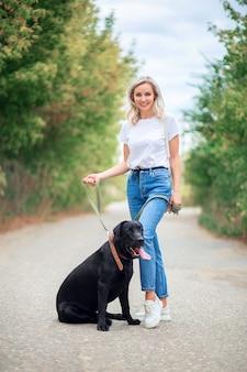 Mooie jonge vrouw in spijkerbroek loopt met haar labradorhond