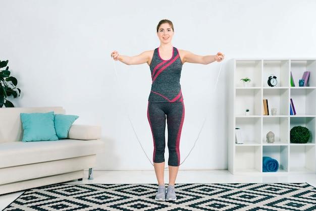 Mooie jonge vrouw in sportkleding die touwtjespringen houdt