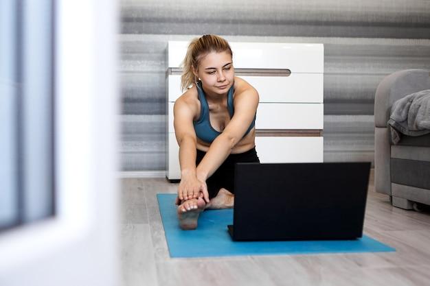 Mooie jonge vrouw in sportkleding kijken naar online video op laptop en oefeningen thuis doen. opleiding op afstand met personal trainer, online onderwijs