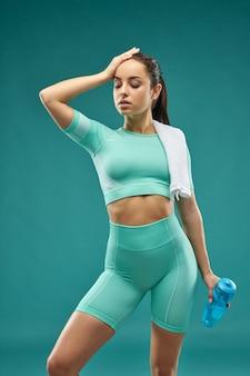 Mooie jonge vrouw in sportkleding met fles water