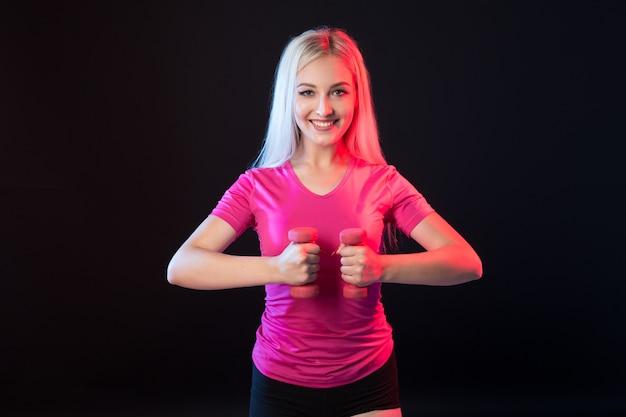 Mooie jonge vrouw in sportkleding op zwart met halters in handen