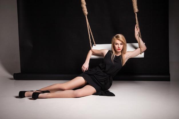 Mooie jonge vrouw in stijlvolle zwarte jurk en zwarte schoenen poseren op een vloer door te schommelen in een studio