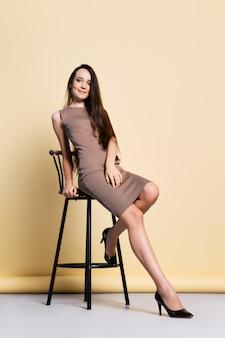 Mooie jonge vrouw in strakke gebreide jurk, lang steil zwart haar en schoenen met hoge hakken zit op een hoge stoel