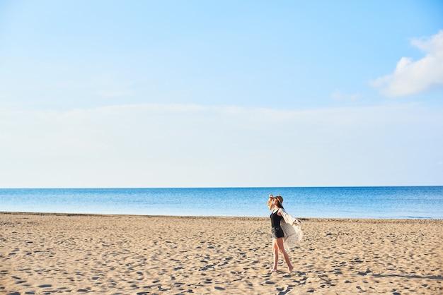 Mooie jonge vrouw in strohoed op het strand