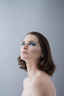 Mooie jonge vrouw in studio op grijze achtergrond.