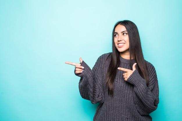 Mooie jonge vrouw in sweater die kant richt en op turkoois glimlacht.