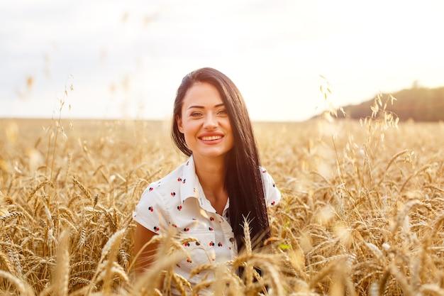 Mooie jonge vrouw in tarweveld schattig brunette meisje van kaukasische verschijning in casual kleding is...