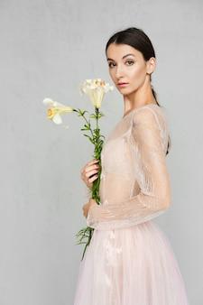 Mooie jonge vrouw in transparante tule jurk met kant poseren met bloemen in de hand