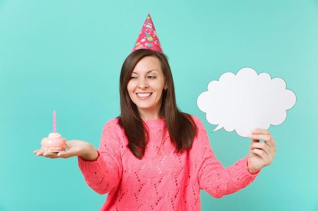 Mooie jonge vrouw in verjaardagshoed met cake met kaars, lege blanco say cloud, tekstballon voor promotionele inhoud geïsoleerd op blauwe achtergrond. mensen levensstijl concept. bespotten kopie ruimte.