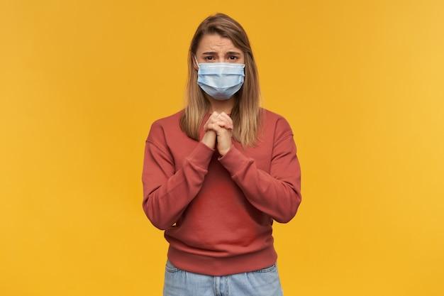 Mooie jonge vrouw in virus beschermend masker op gezicht tegen coronavirus houdt de handen in biddende positie en gele muur