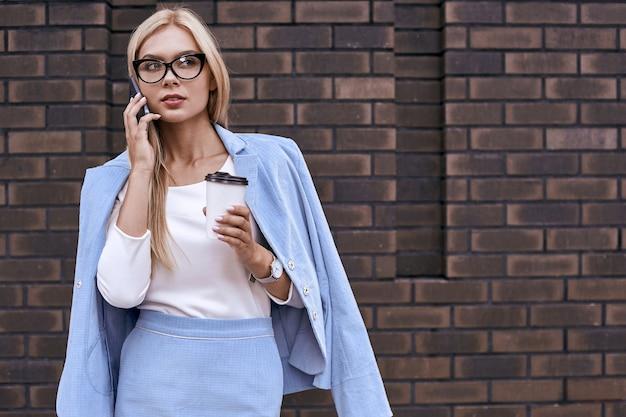 Mooie jonge vrouw in vrijetijdskleding en bril praat op haar telefoon