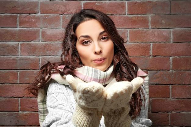 Mooie jonge vrouw in warme kleren die zich dichtbij bakstenen muur bevindt