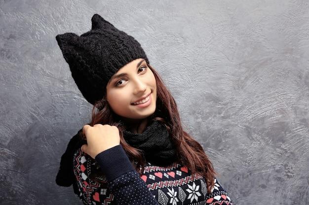 Mooie jonge vrouw in warme kleren die zich dichtbij grijze getextureerde muur bevindt