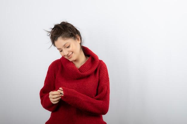 Mooie jonge vrouw in warme rode trui poseren.