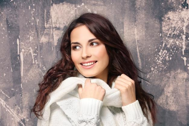 Mooie jonge vrouw in warme trui op grunge background
