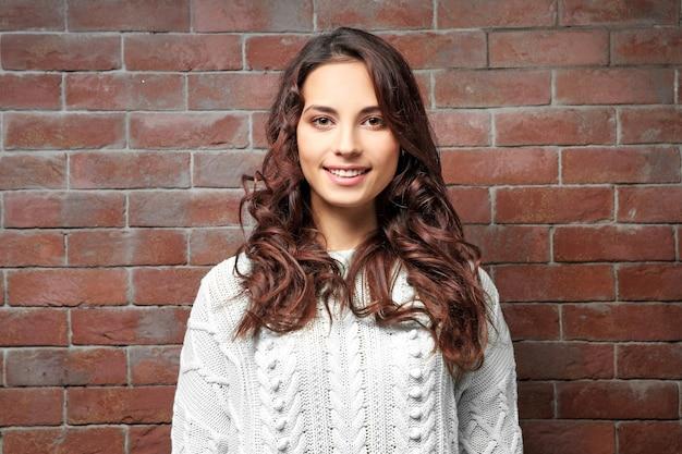 Mooie jonge vrouw in warme trui staande in de buurt van bakstenen muur