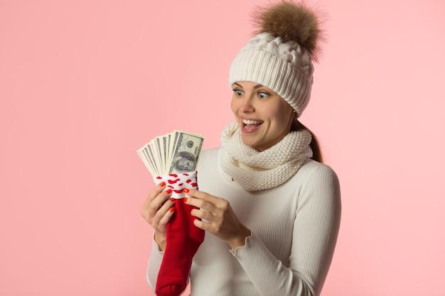 Mooie jonge vrouw in winter hoed met rode sokken met geld