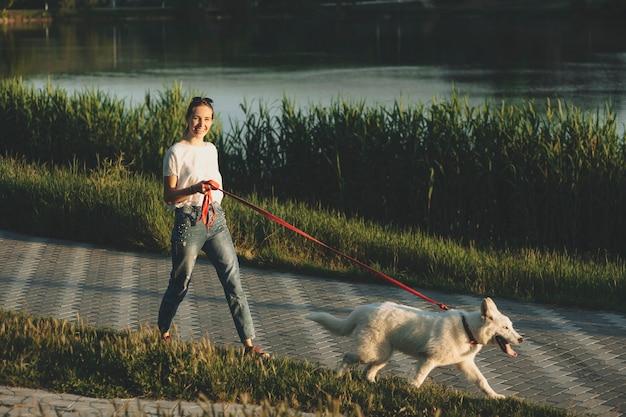 Mooie jonge vrouw in wit overhemd en spijkerbroek lopen aan de leiband schattige witte hond met tong uit bij zonsondergang en kijken naar camera met gras en water op achtergrond