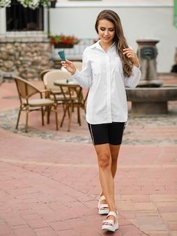 Mooie jonge vrouw in wit overhemd en zwarte korte broek die buiten loopt en een ijsje eet