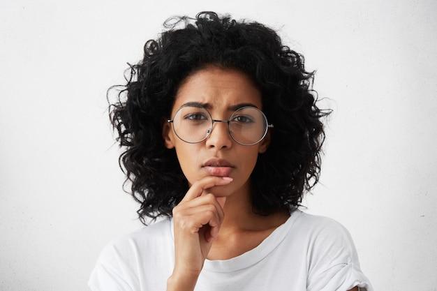 Mooie jonge vrouw in wit t-shirt en grote ronde bril die in haar ogen knijpt