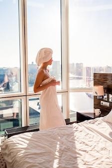 Mooie jonge vrouw in witte badhanddoek bij het hoofd ontspannen na douche op bed met kop van koffie