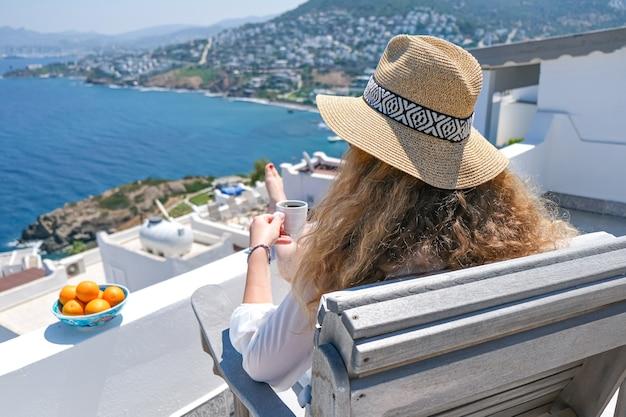 Mooie jonge vrouw in witte jurk en strooien hoed en koffiekopje zittend op wit terras balkon van huis of hotel met uitzicht op zee.