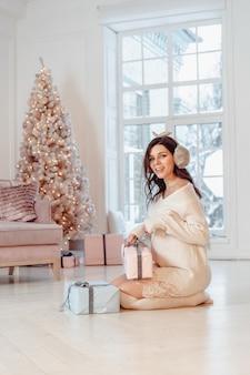 Mooie jonge vrouw in witte jurk poseren met geschenkdozen