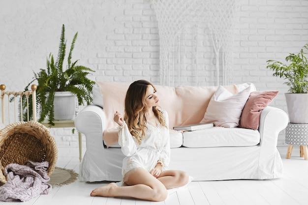 Mooie jonge vrouw in witte satijnen pyjama's zit op de vloer in de buurt van de bank in een wit interieur.
