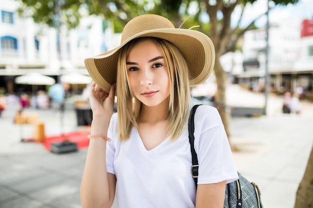 Mooie jonge vrouw in zomerhoed wandelen in de stad.