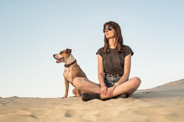 Mooie jonge vrouw in zonnebril met hond zit op zand. meisje in vrijetijdskleding wandelen en staffordshire terriër puppy zittend op zandstrand of in de woestijn op warme zonnige dag