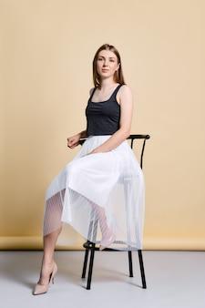 Mooie jonge vrouw in zwart mouwloos onderhemd en witte rokzitting op lange stoel over lichtgeel