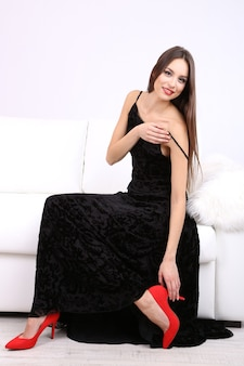 Mooie jonge vrouw in zwarte jurk op de bank