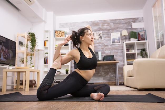 Mooie jonge vrouw in zwarte sportkleding die een benen yoga pose doet in de woonkamer.