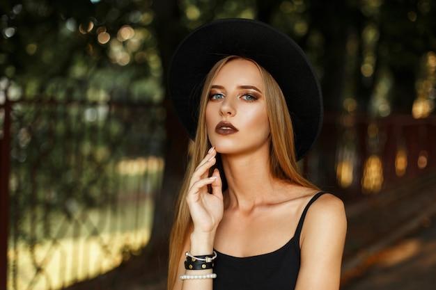 Mooie jonge vrouw in zwarte stijlvolle kleding en een modieuze hoed