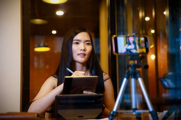 Mooie jonge vrouw influencer vlogger in vrijetijdskleding glimlachend tijdens het opnemen van video
