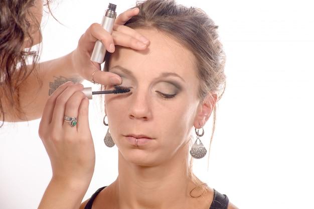 Mooie jonge vrouw is make-up