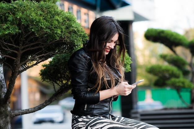 Mooie jonge vrouw is sms op haar smartphone zittend op het bankje in het stadspark