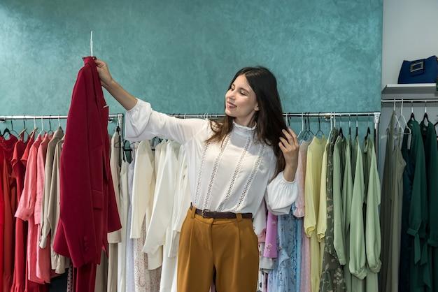 Mooie jonge vrouw jas kiezen bij kledingwinkel. nieuwe stijl