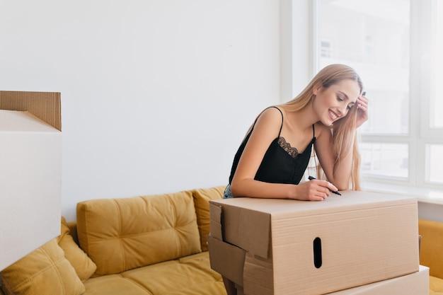 Mooie jonge vrouw kartonnen doos labelen, marker in de hand houden, spullen gaan pakken, verhuizen naar nieuw appartement, flat, huis. gelukkig meisje in de kamer met gele bank, ze draagt zwarte top.