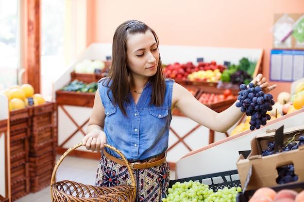 Mooie jonge vrouw kiest druiven in een groentewinkel