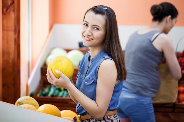 Mooie jonge vrouw kiest meloenen in een groentewinkel