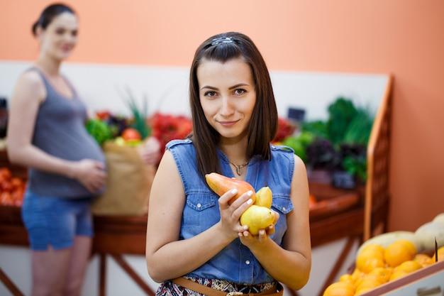 Mooie jonge vrouw kiest peren bij een supermarkt