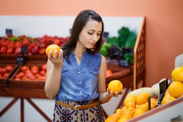 Mooie jonge vrouw kiest sinaasappelen in een groente winkel
