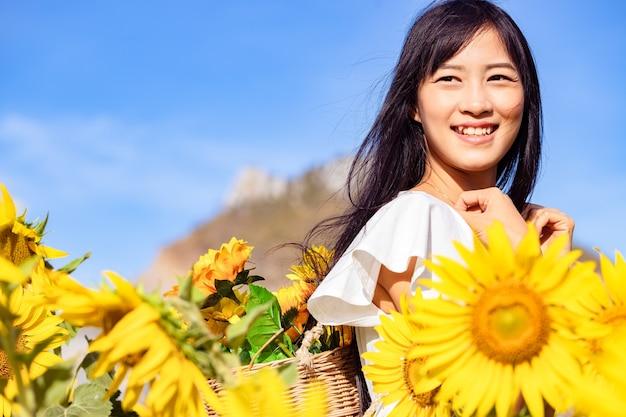 Mooie jonge vrouw kijken naar de fotograaf in een veld met zonnebloemen in een witte jurk.