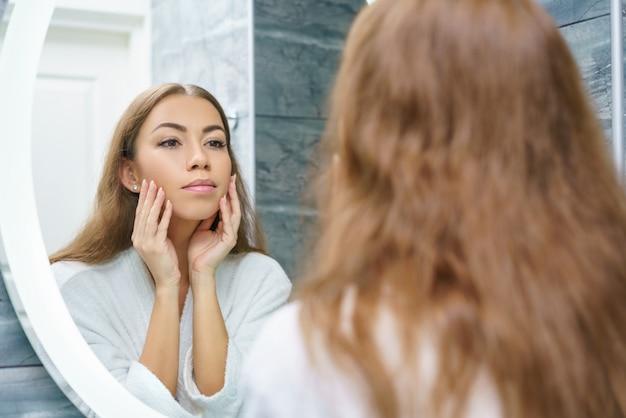 Mooie jonge vrouw kijkt naar haar gezicht in de spiegel