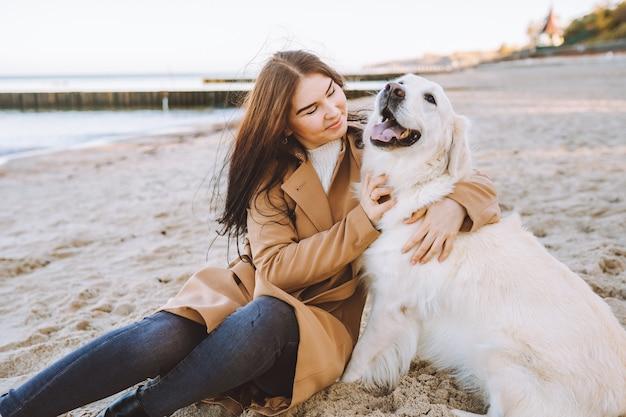 Mooie jonge vrouw knuffelen met haar gouden retreiver hond op het strand op warme herfstdag.