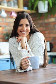 Mooie jonge vrouw koffie of thee drinken in de keuken