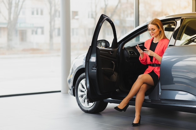 Mooie jonge vrouw koopt een auto in de salon van de dealer