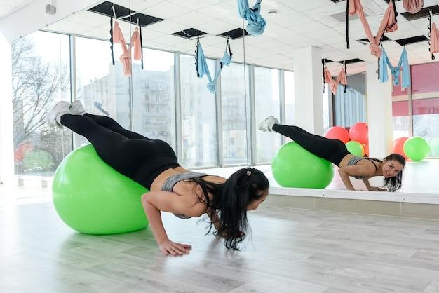Mooie jonge vrouw kracht oefening op fit bal in aerobics klasse studio. vrouwelijke fitness als levensstijl en gezondheid.