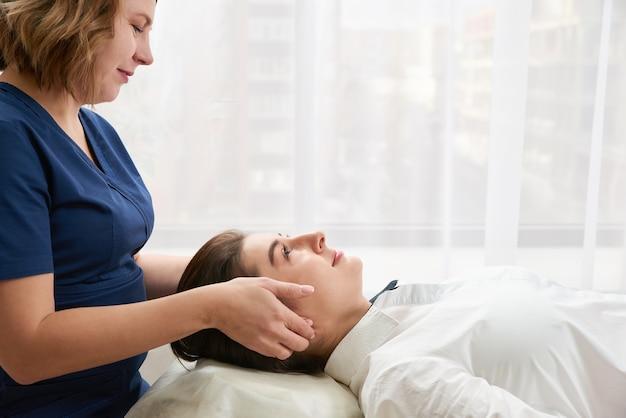 Mooie jonge vrouw krijgt een gezicht en een hoofdbehandeling bij schoonheidssalon